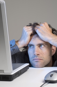 bigstockphoto_Man_Looking_At_Computer_In_Des_5307220[1]